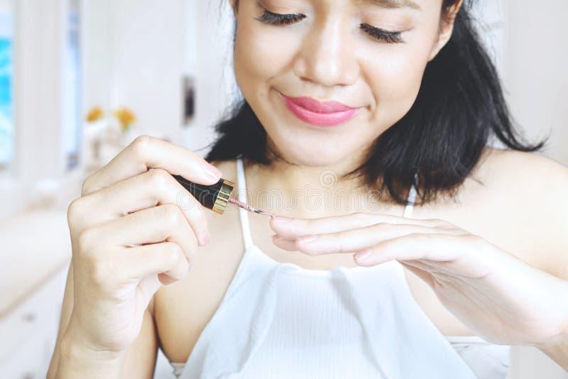 Mooie vrouw die nagellak toepast royalty-vrije stock afbeelding