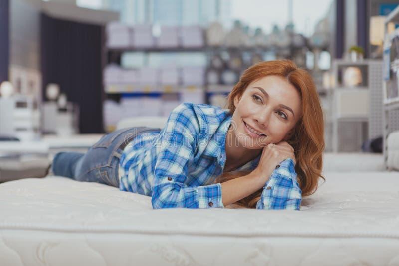 Mooie vrouw die nieuwe matras kopen bij meubilairopslag royalty-vrije stock afbeelding