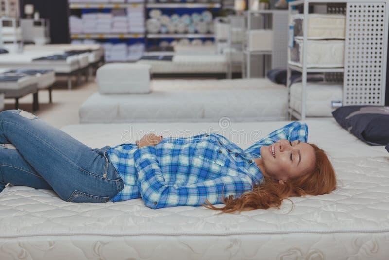 Mooie vrouw die nieuwe matras kopen bij meubilairopslag stock foto