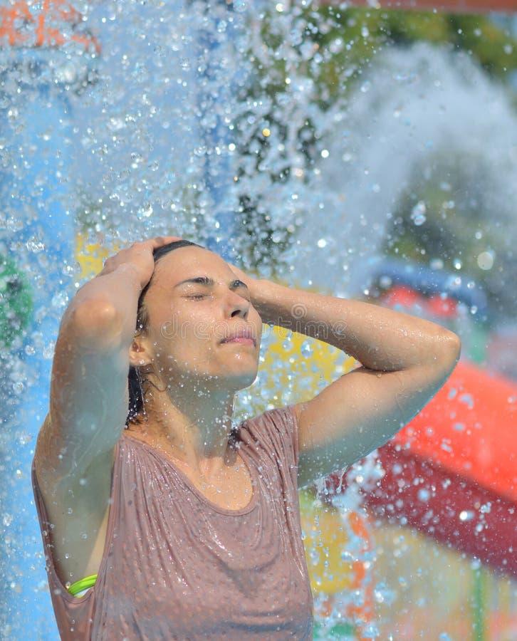 Mooie vrouw die onder een waterstraal genieten van met rond duizenden dalingen stock fotografie