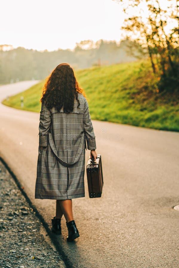 Mooie vrouw die onderaan de weg weggaan royalty-vrije stock fotografie