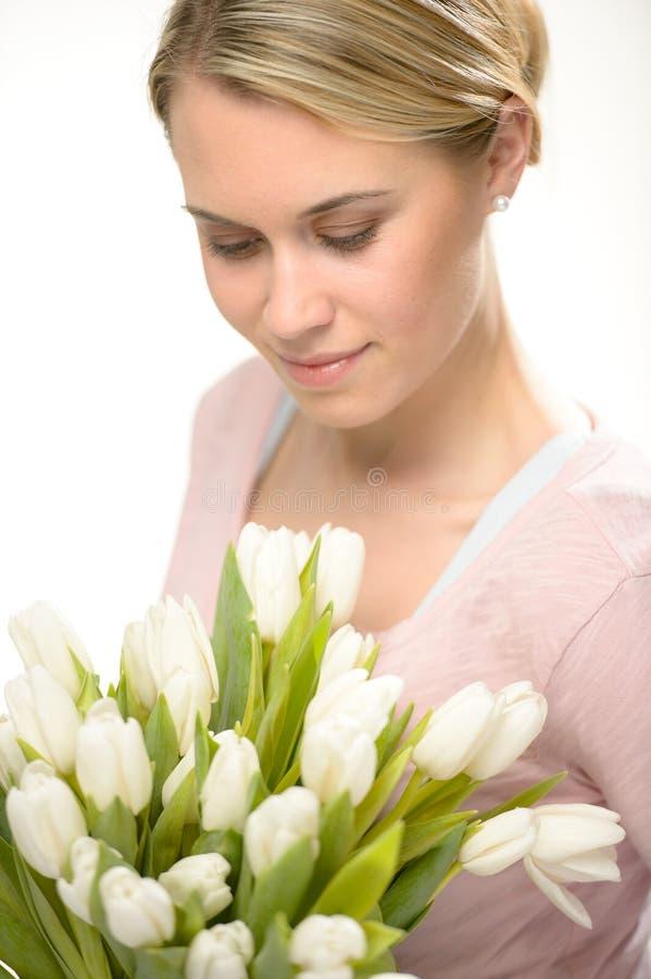 Mooie vrouw die onderaan witte tulpenbloemen kijken royalty-vrije stock afbeelding