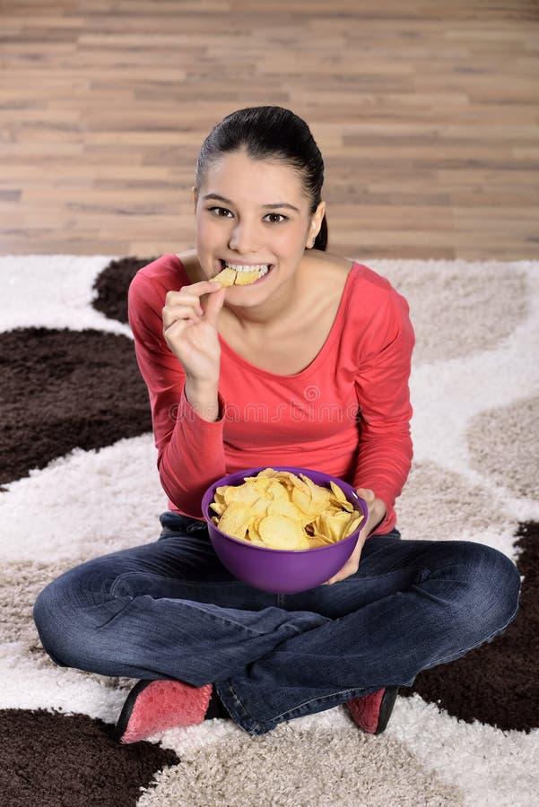 Mooie vrouw die ongezonde kost eten royalty-vrije stock afbeelding