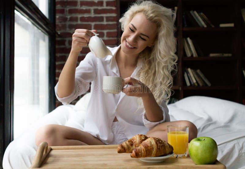 Mooie Vrouw die Ontbijt in Bed hebben royalty-vrije stock foto's