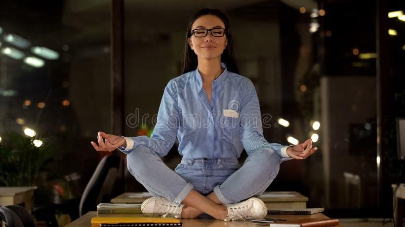 Mooie vrouw die op bureau, onderbrekingstijd mediteren om productiviteit op te voeren stock afbeeldingen