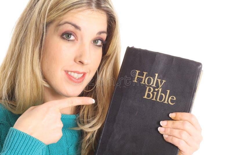 Mooie vrouw die op de bijbel richt stock fotografie