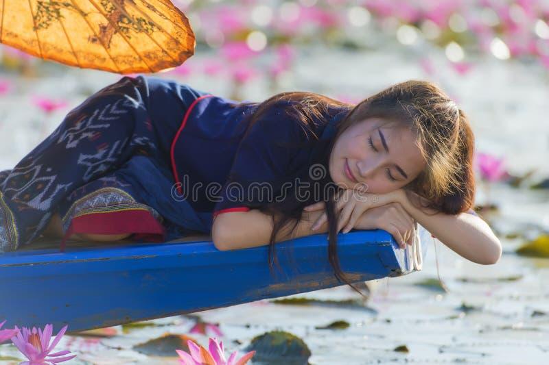 Mooie vrouw die op de boot in rood lotusbloemmeer liggen stock afbeelding