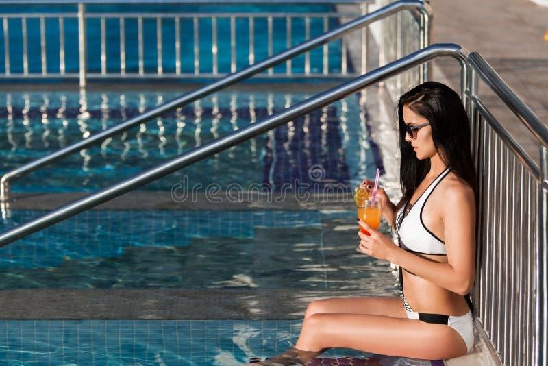 Mooie vrouw die op de omheining van een zwembad leunen stock afbeeldingen