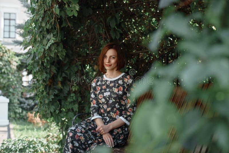 Mooie vrouw, die op een bank tegen groene bladerenachtergrond zitten stock foto