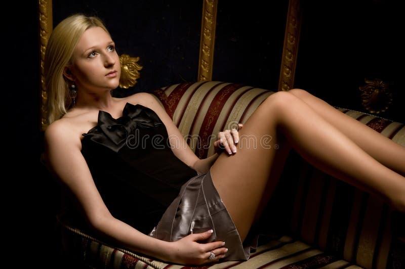 Mooie vrouw die op een leerbank ligt royalty-vrije stock fotografie
