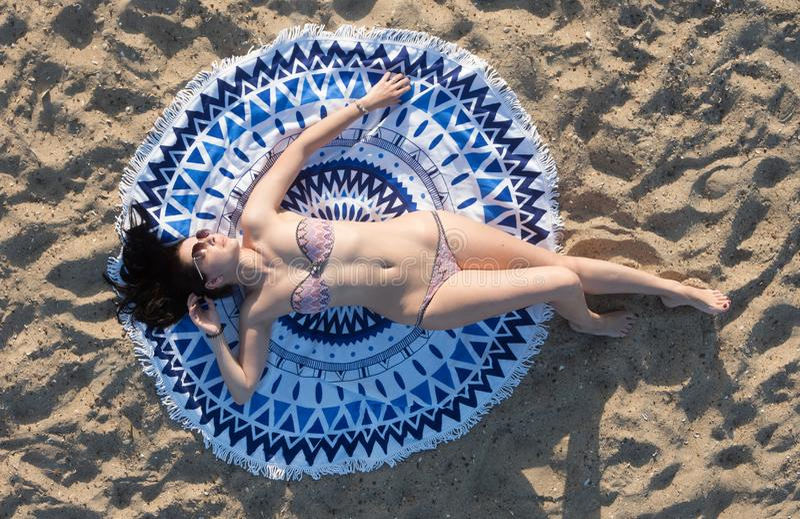 Mooie vrouw die op een mandala om strandtapijtwerk liggen stock foto's