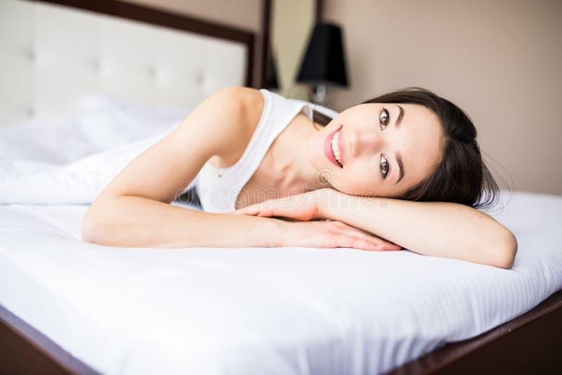 Mooie vrouw die op haar bed thuis in de ochtend liggen stock foto