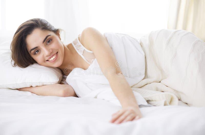 Mooie vrouw die op haar bed thuis liggen royalty-vrije stock foto's