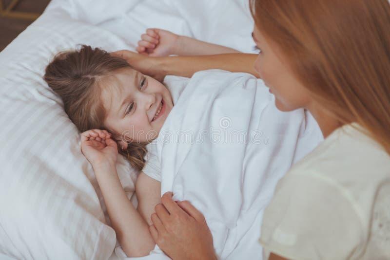 Mooie vrouw die op haar dochterslaap letten stock fotografie