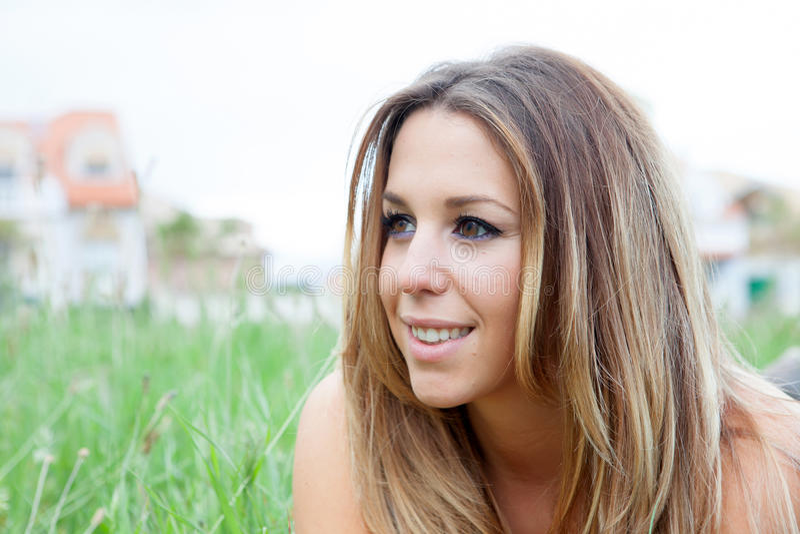Mooie vrouw die op het gras ligt stock afbeelding