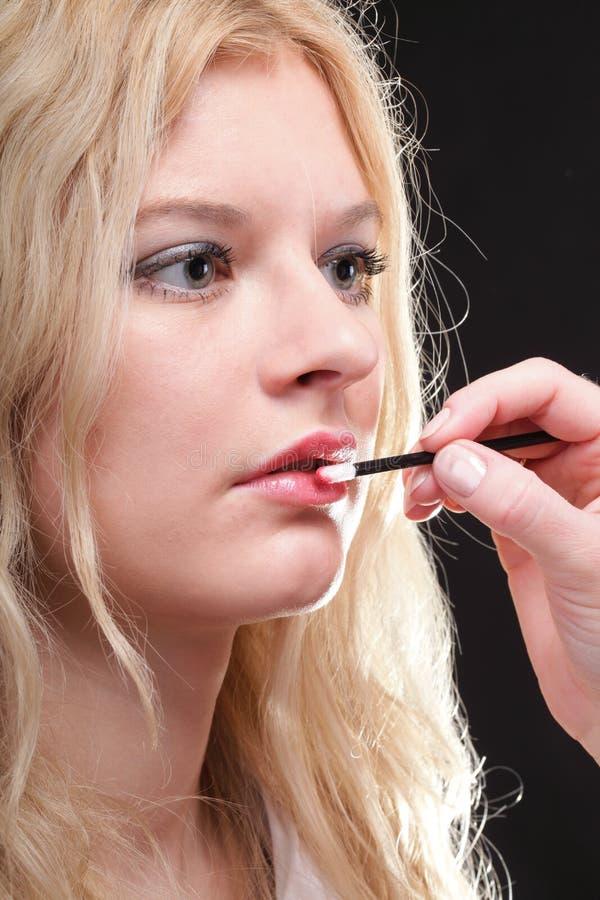 Mooie vrouw die op make-up zetten royalty-vrije stock foto