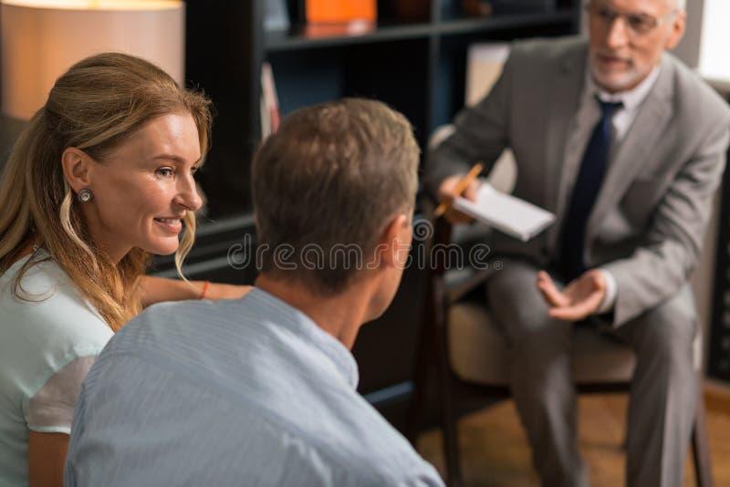 Mooie vrouw die op middelbare leeftijd terwijl het bekijken haar echtgenoot glimlachen royalty-vrije stock foto