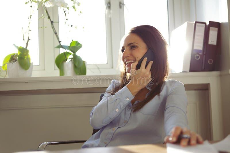 Mooie vrouw die op mobiele telefoon in huisbureau spreken royalty-vrije stock foto's