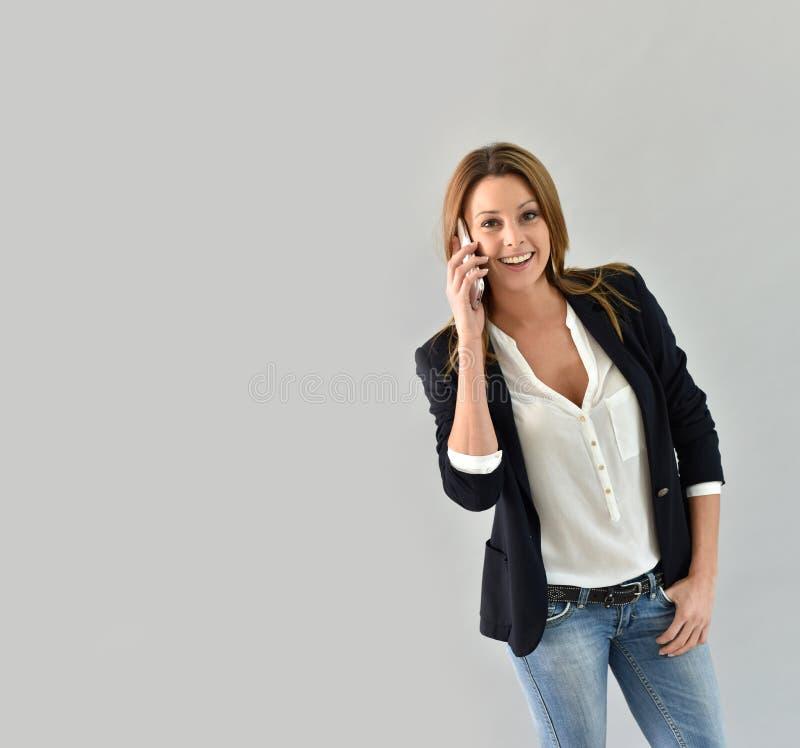 Mooie in vrouw die op telefoon spreken stock fotografie