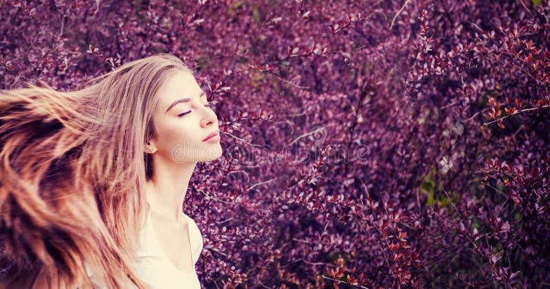 Mooie vrouw die in openlucht van tegen purpere bloemenachtergrond genieten stock fotografie