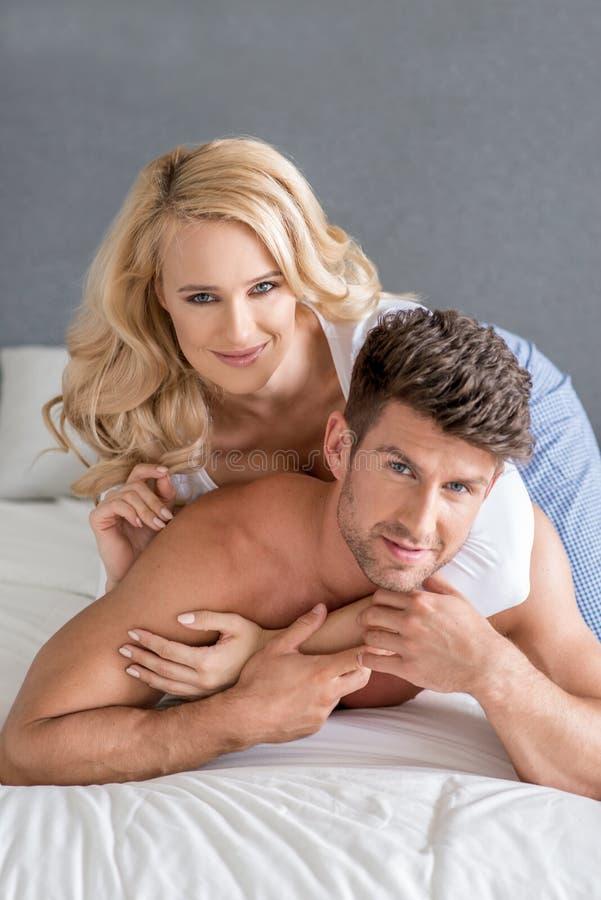 Mooie Vrouw die over Knappe Partner op Bed ligt royalty-vrije stock afbeeldingen