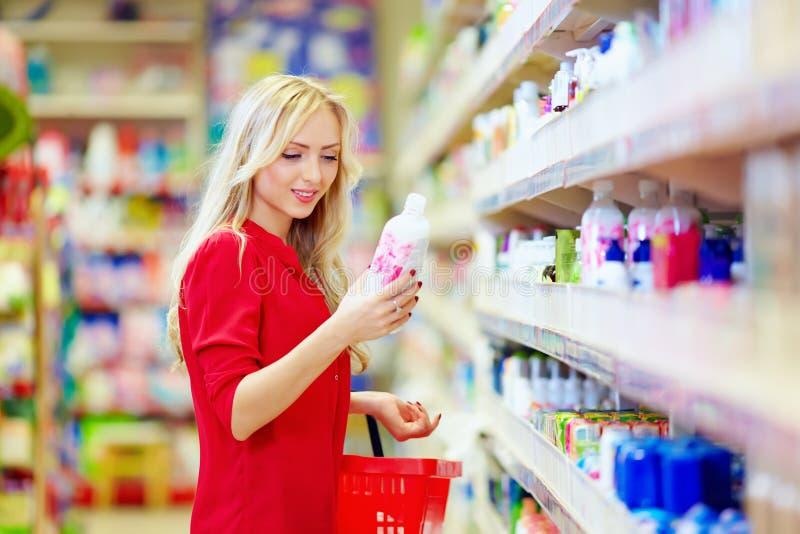 Mooie vrouw die persoonlijke verzorgingproduct in supermarkt kiezen stock fotografie