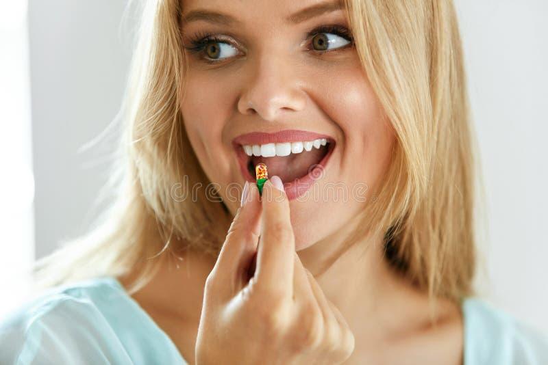 Mooie Vrouw die Pil, Geneeskunde nemen Vitaminen en supplementen stock foto