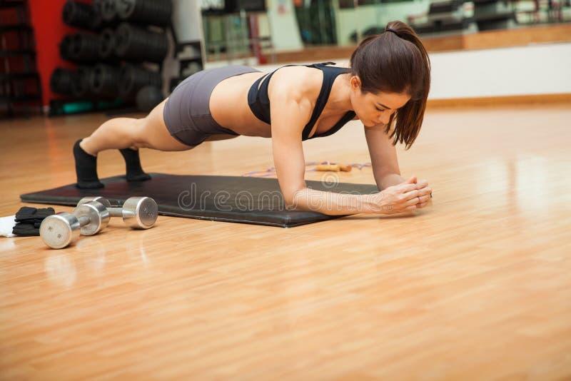 Mooie vrouw die planken doen bij een gymnastiek stock foto