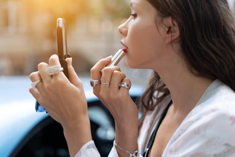 Mooie vrouw die rode lipstic en het doen snelle make-up houden royalty-vrije stock fotografie