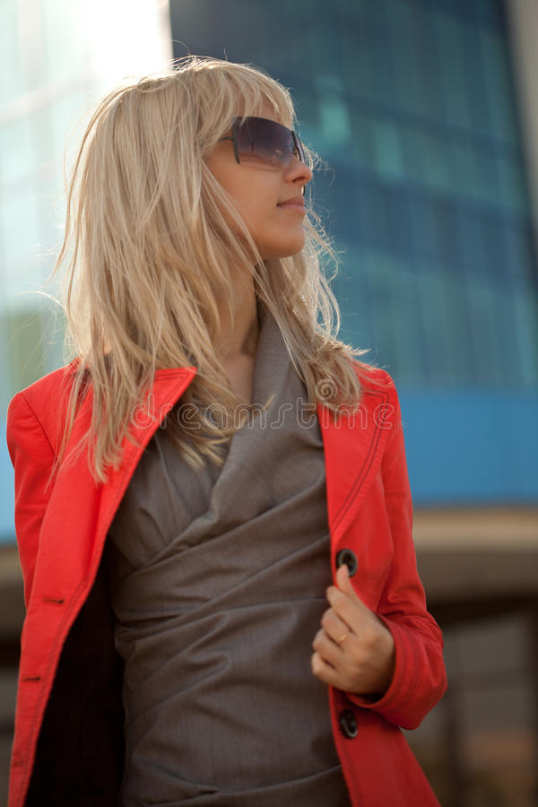 Mooie vrouw die in rood jasje in de stad lopen stock foto's
