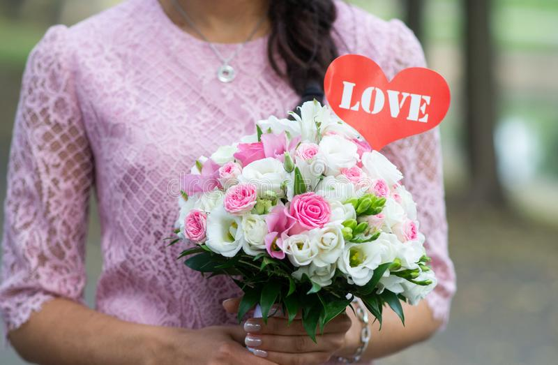 Mooie vrouw die in roze kleding een huwelijksboeket van bloemen houden, de zomertijd, liefde, de dag van Valentine stock afbeelding