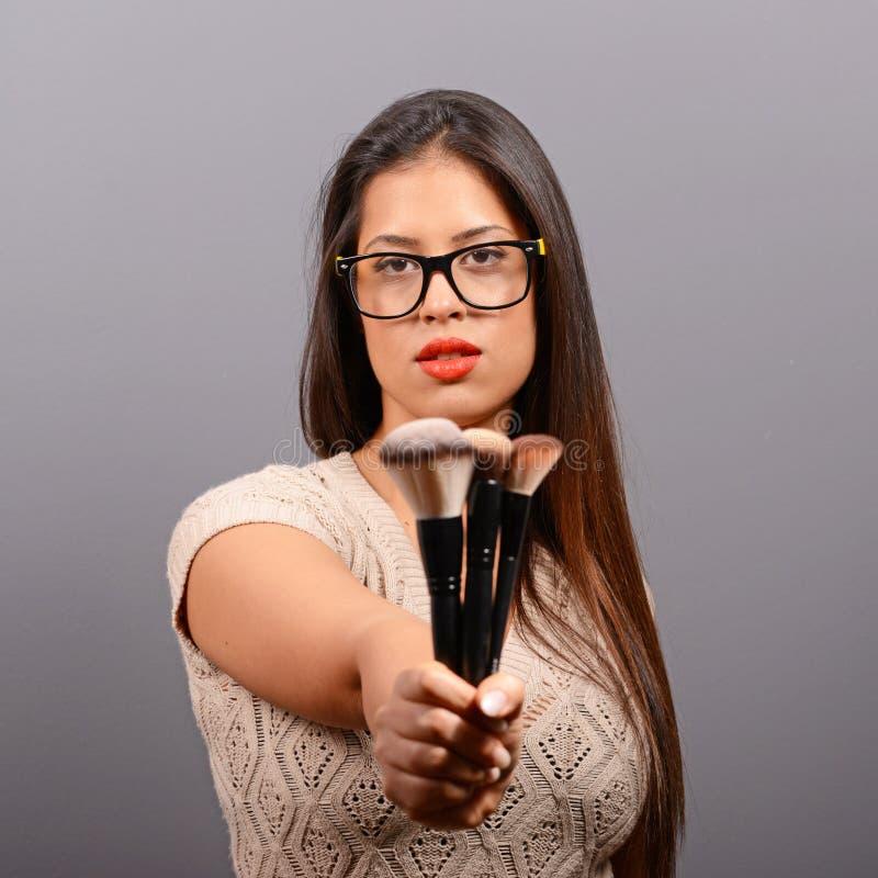 Mooie vrouw die samenstelling op gezicht met kosmetische borstel doet Mannequin het stellen tegen grijze achtergrond stock fotografie