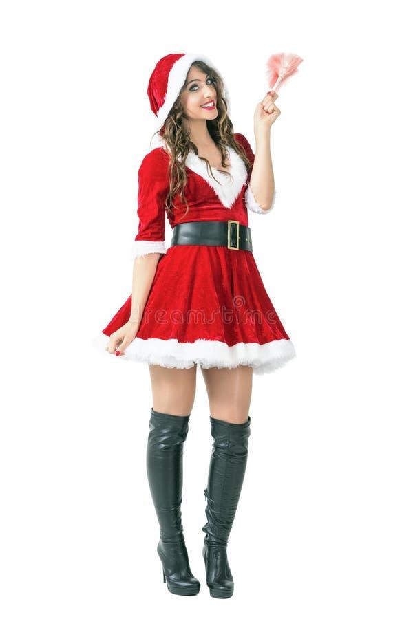 Mooie vrouw die in Santa Claus-kostuum roze stofdoekborstel houden glimlachend bij camera stock afbeelding