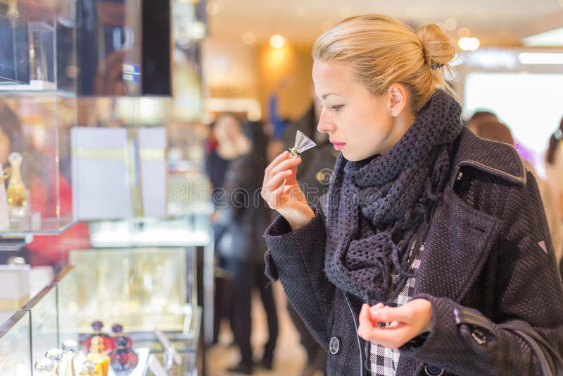 Mooie vrouw die in schoonheidsopslag winkelen stock afbeeldingen
