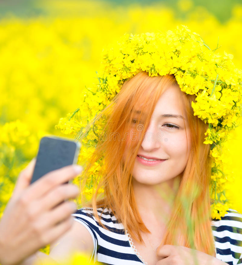 Mooie vrouw die selfie beeld van zich op geel gebied met natuurlijke achtergrond nemen stock foto