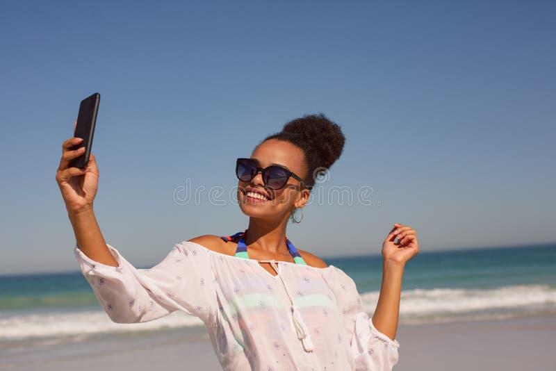 Mooie vrouw die selfie met mobiele telefoon bij strand in de zonneschijn nemen stock afbeeldingen