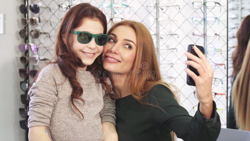 Mooie vrouw die selfies met haar leuke dochter bij de eyewear opslag nemen royalty-vrije stock afbeeldingen