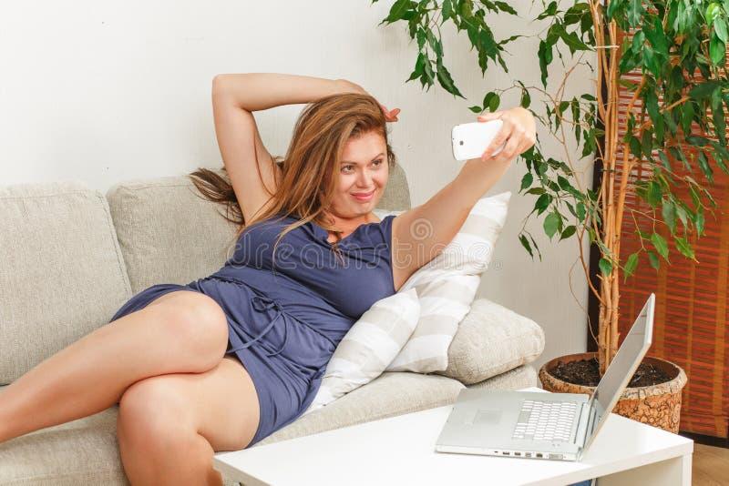 Mooie vrouw die selfies thuis maken stock foto's
