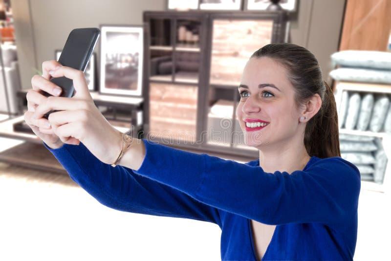 Mooie vrouw die smartphone in huis met behulp van selfie stock afbeelding
