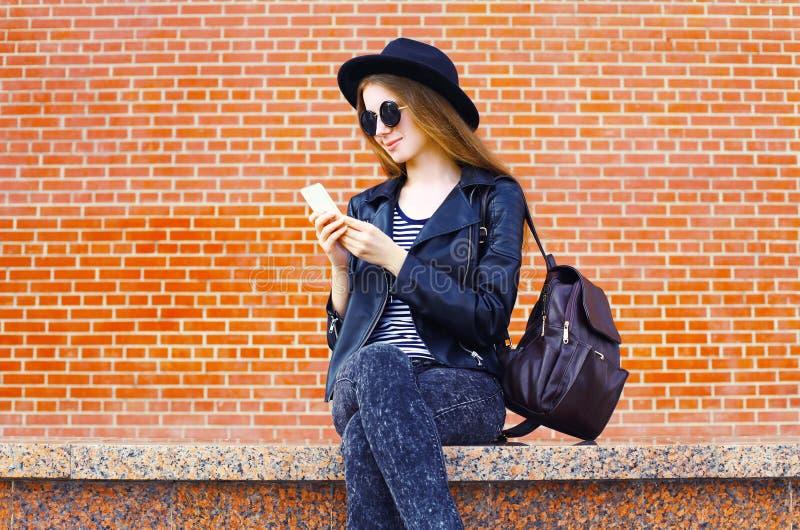 Mooie vrouw die smartphone in rots zwarte stijl gebruiken over bakstenen royalty-vrije stock foto