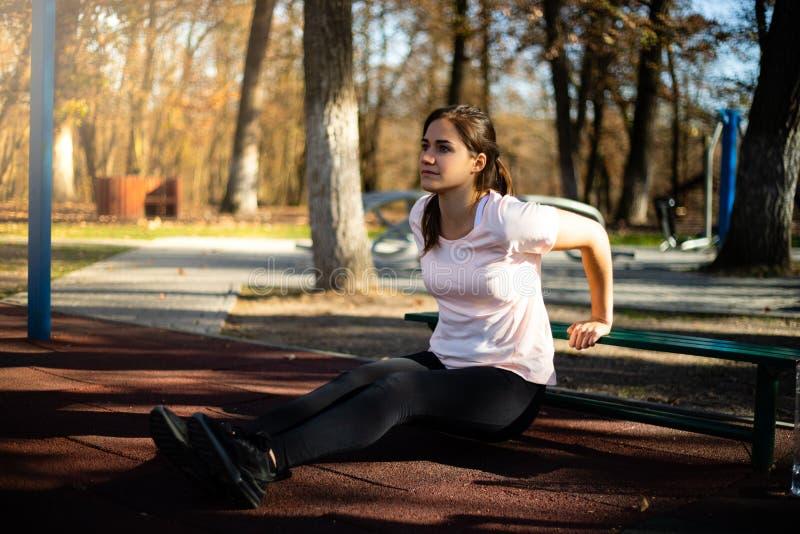 Mooie vrouw die sport op openluchtpark doen tijdens daling en zonsondergang - de triceps oefent uit stock foto