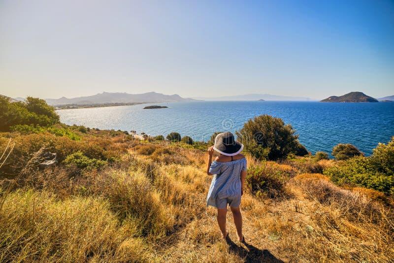 Mooie vrouw die in strandhoed van overzeese mening met blauwe hemel genieten bij zonnige dag in Bodrum, Turkije De Zomer van het  stock foto
