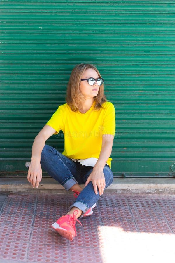 Mooie vrouw die t-shirt, jeans en zonnebril dragen, die op het voetgebied dichtbij de stadsbouw zitten royalty-vrije stock foto