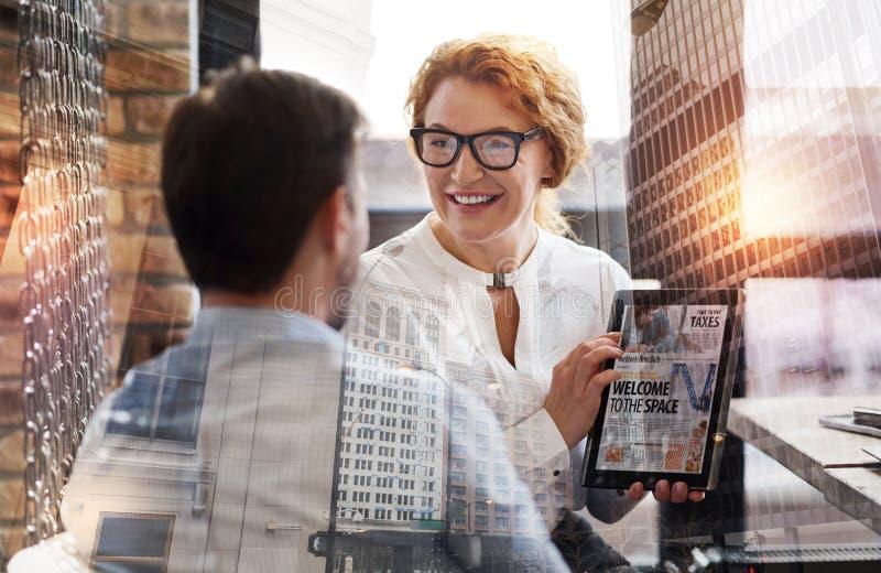 Mooie vrouw die tablet met nieuwsartikel tonen aan haar werkgever stock foto