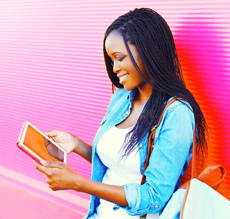 Mooie vrouw die tabletpc in de stad over kleurrijk roze met behulp van stock fotografie