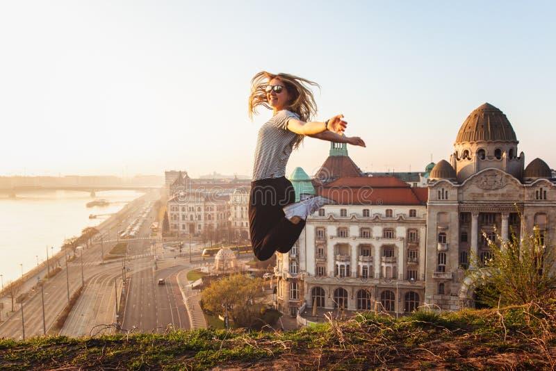 Mooie vrouw die tegenover beroemde voorgevel en ingang aan Hotel Gellert op banken van Donau in Boedapest, Hongarije springen royalty-vrije stock foto