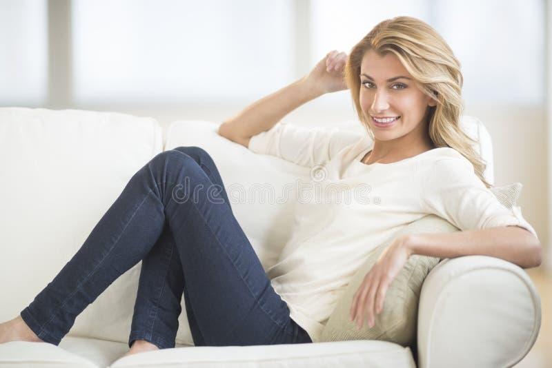 Mooie Vrouw die terwijl het Ontspannen op Bank glimlachen stock afbeeldingen