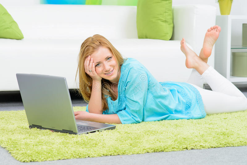 mooie vrouw die thuis bij vloer met laptop leggen stock foto