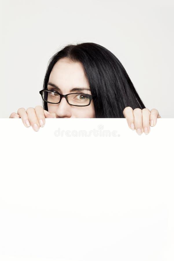 Mooie vrouw die tonend leeg wit aanplakbiljet glimlachen stock afbeelding