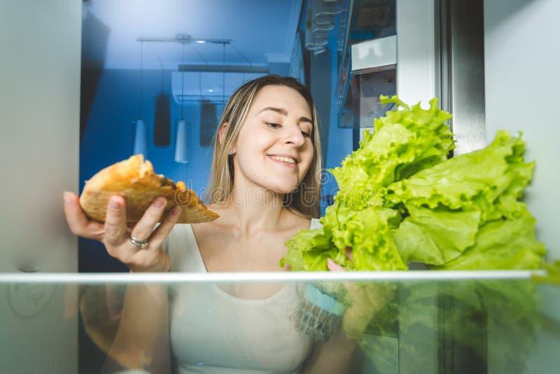 Mooie vrouw die tussen pizza en verse salade kiezen Mening voor royalty-vrije stock foto's